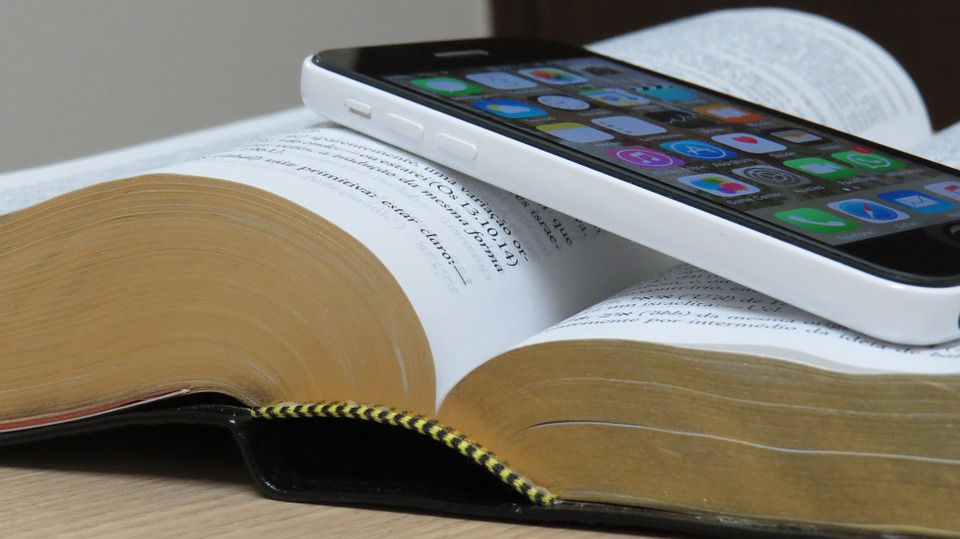 open Bible with an iPhone laying on top of the open pages