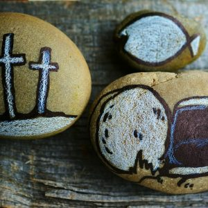 three small decorative stones, one with three crosses, one with a fish and the last with a cut loaf of bread