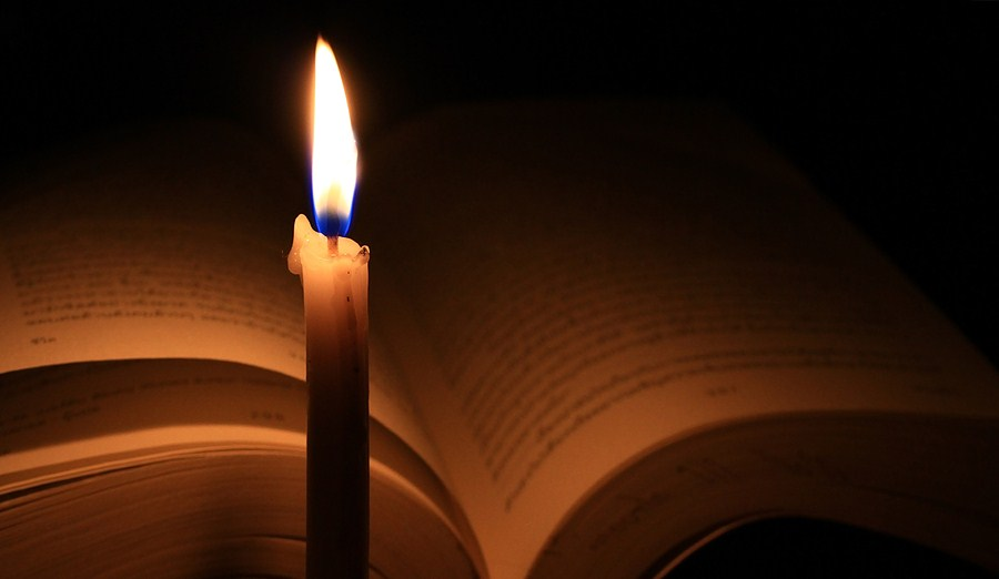 an open Bible in partial darkness with a lighted candle